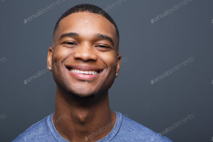 Happy black man smiling on gray background