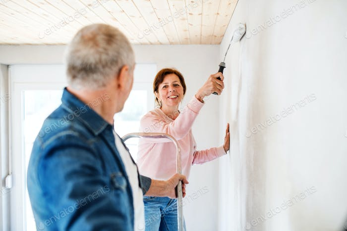 Senior couple painting walls in new home, relocation concept