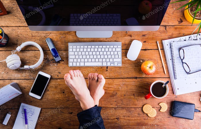 Businessman working in his office with feet on desk