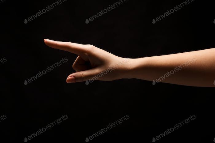 Hand gestures - woman pointing, isolated at black