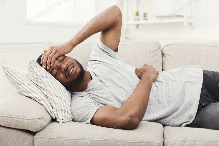 Handsome young african-american man suffering from stomachache and headache