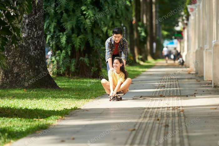 Couple riding on skateboard