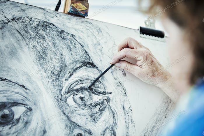 An artist working at her easel, drawing with charcoal on paper