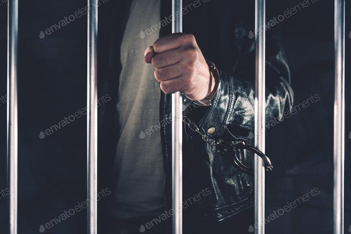 Handcuffed man behind prison bars