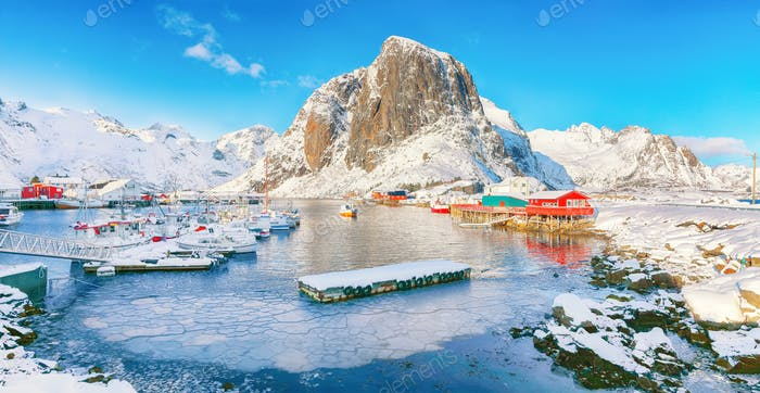 Amazing winter view on Hamnoy village with port and Festhaeltinden mountain on background.
