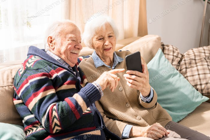 Senior Couple Using Smartphone Indoors