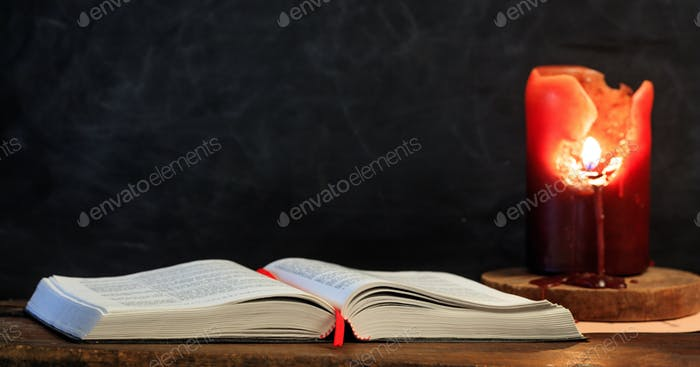 Vintage book and candle on black background