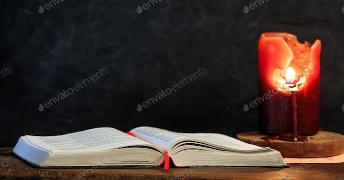 Vintage Buch und Kerze auf schwarzem Hintergrund