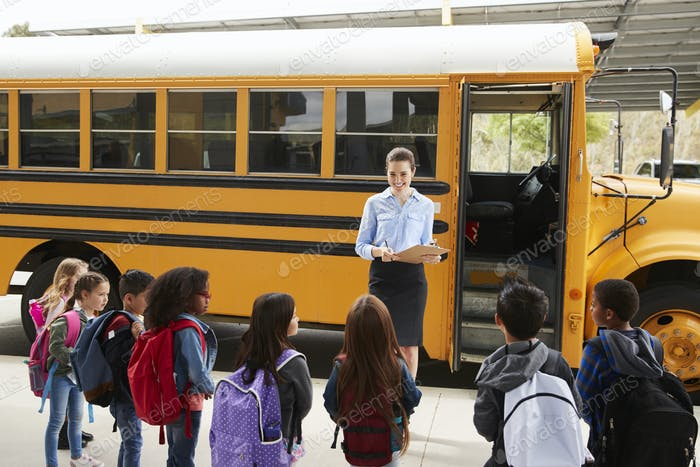 Teacher taking a register of school kids by school bus