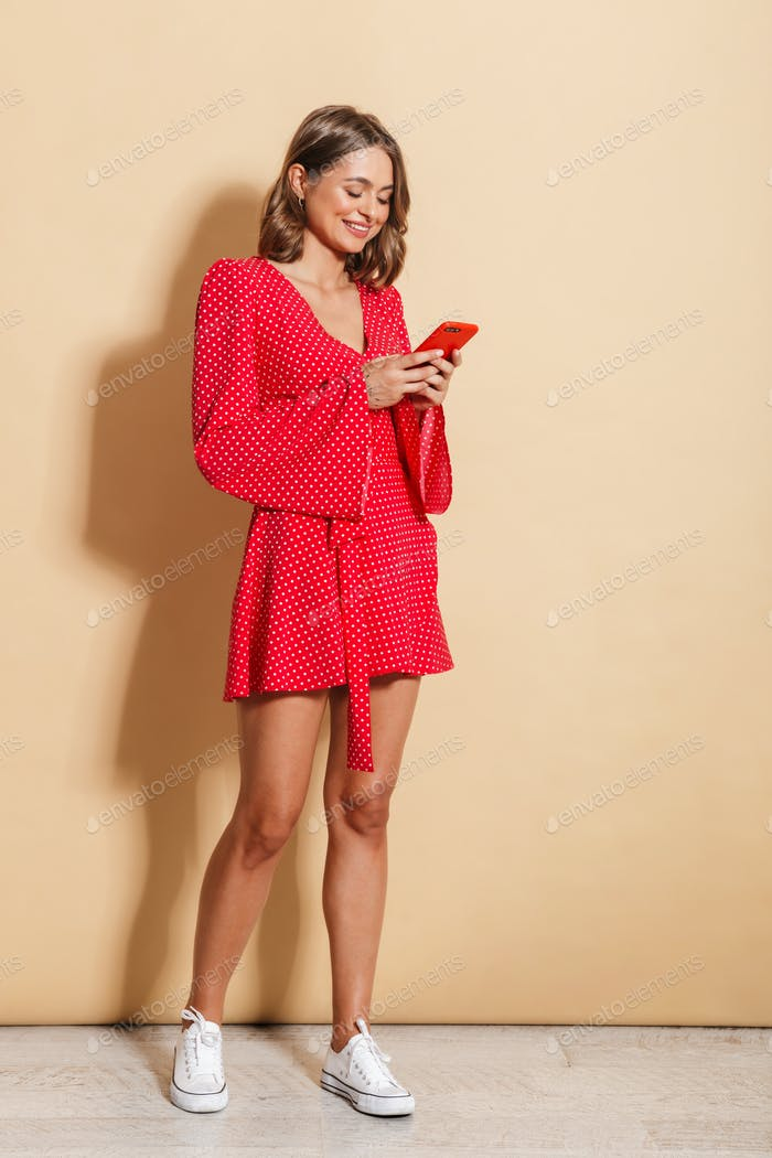 Photo of charming woman wearing red dress smiling and holding cellphone