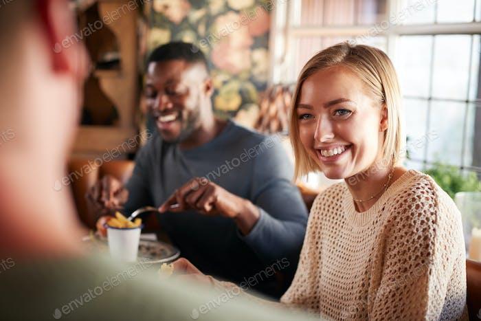 Группа друзей собралась для еды в традиционном английском пабе