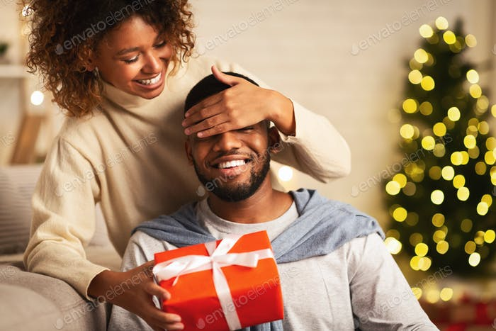 Xmas surprise. Loving wife giving gift to husband