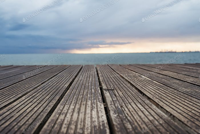 View of wooden decking, sea and gray sky at dusk.