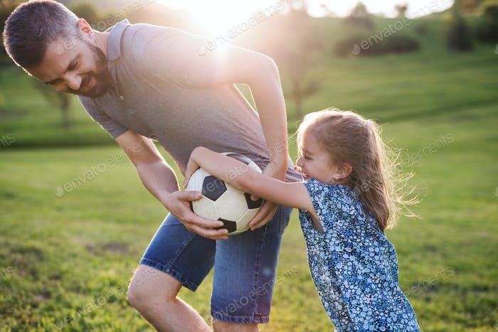 Father with a small daughter playing with a ball in spring nature.