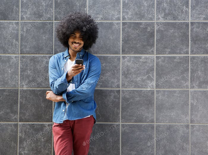 Smiling black man standing with mobile phone outside