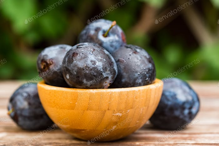 Fresh ripe plums in wooden bowl close