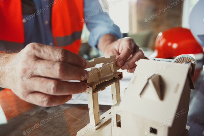 Close up of male architect-engineer making a model of house
