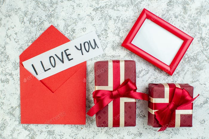 top view i love you written on paper in red envelope red picture frame red giftboxes on grey table