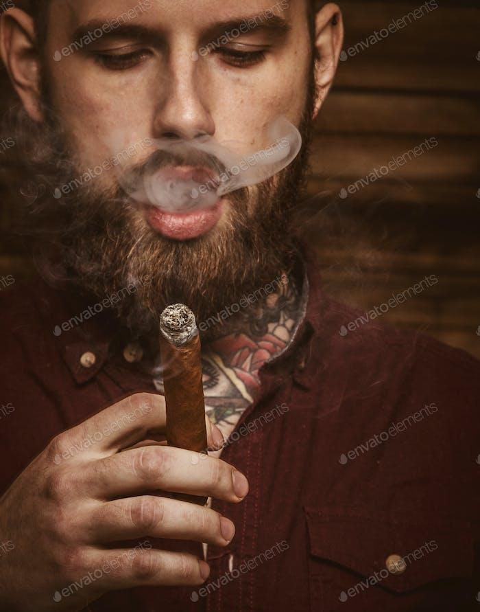 Brutal tätowierte Männchen mit Zigarre