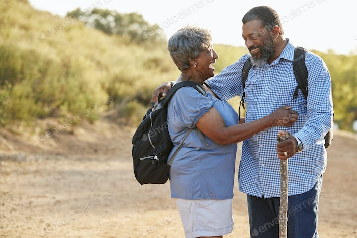 Senior Couple Wearing Backpacks Hiking In Countryside Together
