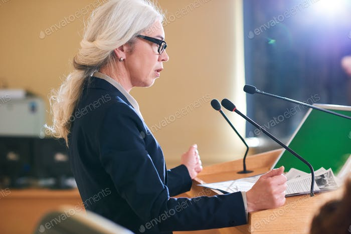 Mature elegant female delegate in suit speaking in microphone