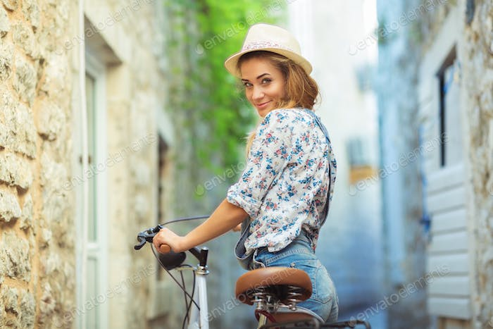 Happy woman with bicycle on street of old town