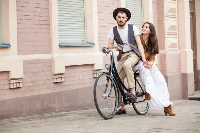 Joven pareja sentado en una bicicleta contra la pared