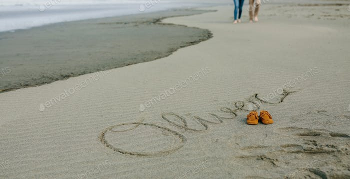 Baby name written in sand with shoes