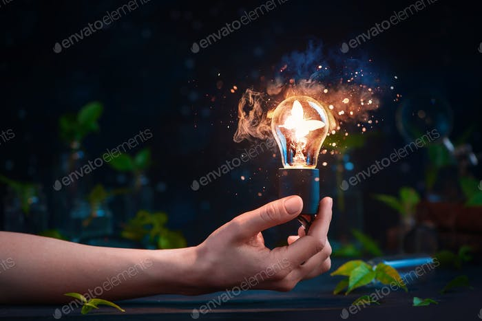 Lightbulb with a butterfly inside in a hand. Merging science and magic