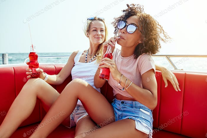 Two friends enjoying drinks on a boat during summer vacation