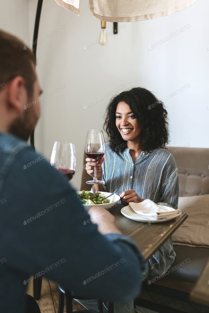 Smiling lady with dark curly hair having dinner with friend in restaurant