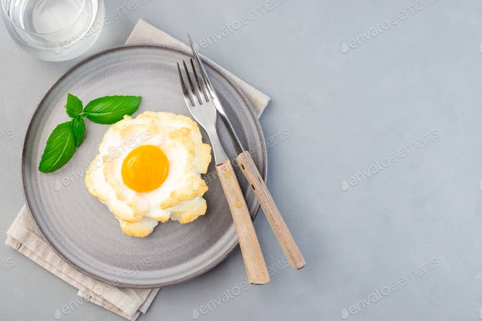 Trendy cloud or fluffy egg dish on gray plate, horizontal, top view, copy space