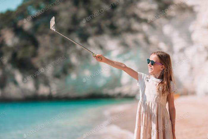 Little girl taking selfie by her smartphone on the beach