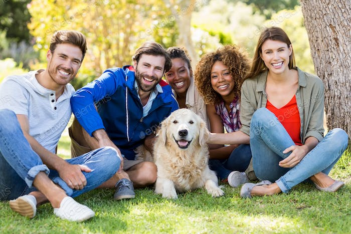 Group of happy friends sitting together with the dog