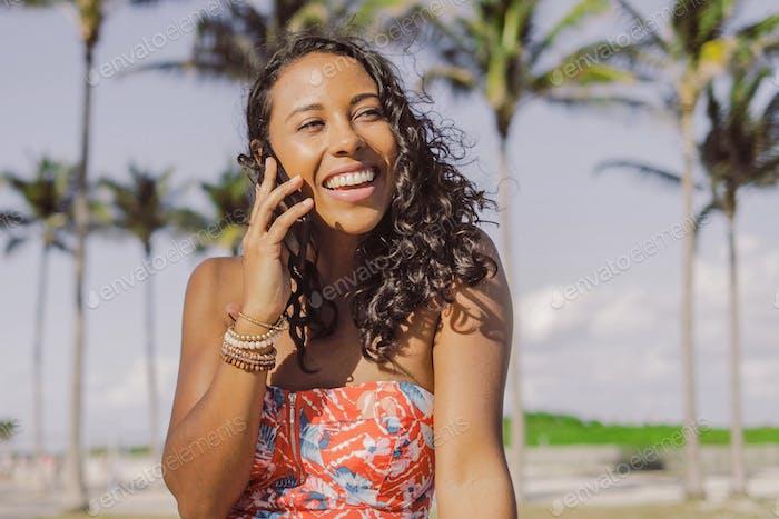 Hübsche ethnische Frau spricht auf Smartphone im Sommer