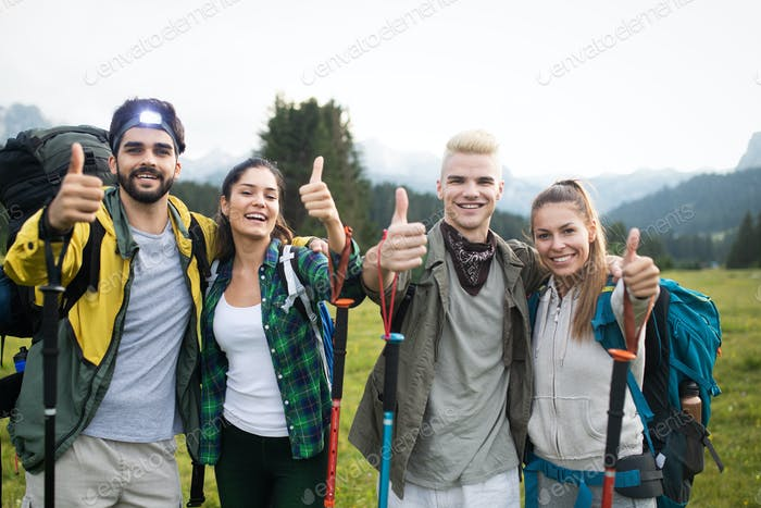 Group of friends on a mountain. Men and women climbing rocks