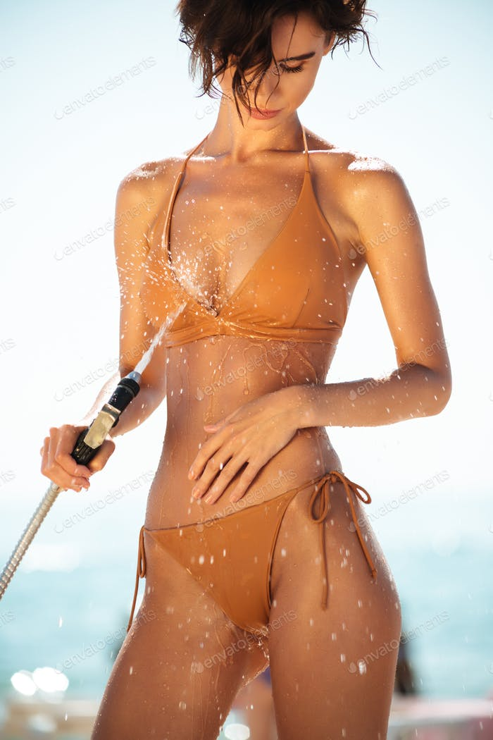 Portrait of lady in beige swimsuit rinsing beach sand off her body on beach