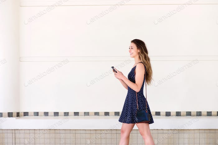 happy woman walking with handbag and  mobile phone