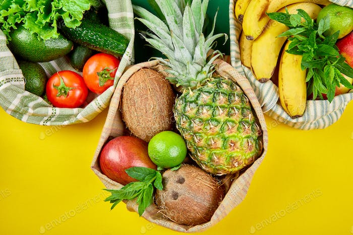 Eco shopping bags with organic fruits and vegetable on yellow background.