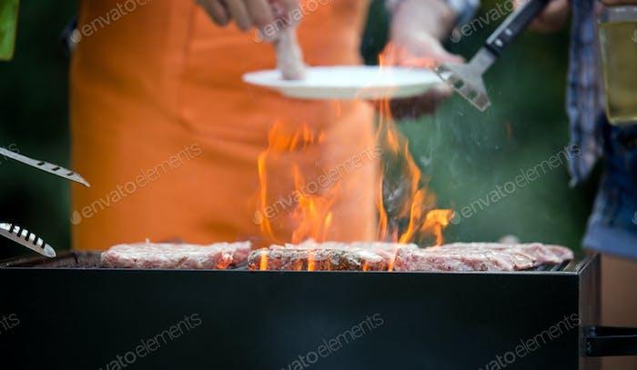 Schöne männliche Vorbereitung Grill im Freien für Freunde