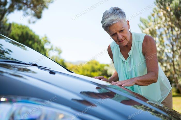 Senior woman checking her car