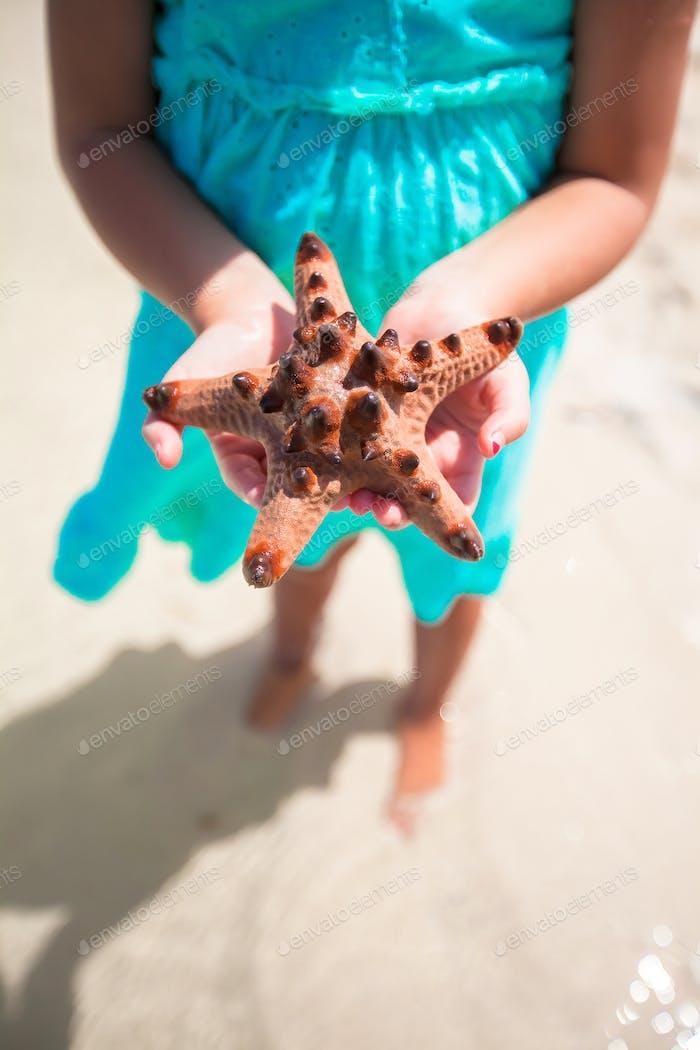 Детские руки держат морскую звезду