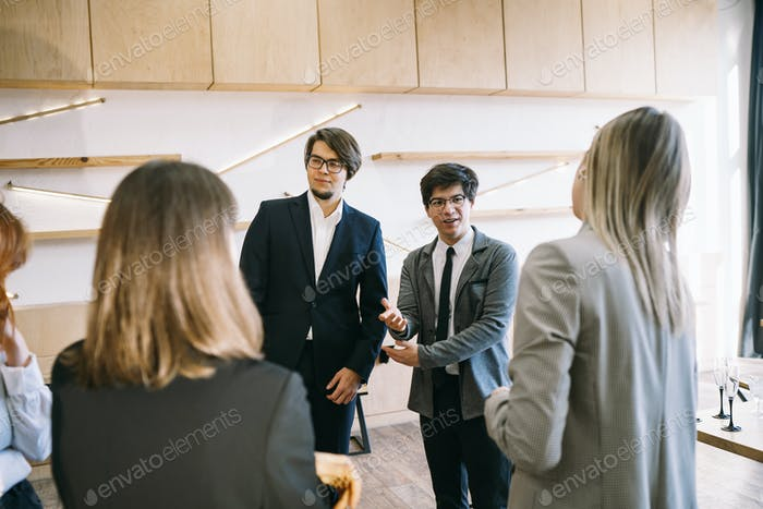 Group of business people in a meeting standing grouped in a office