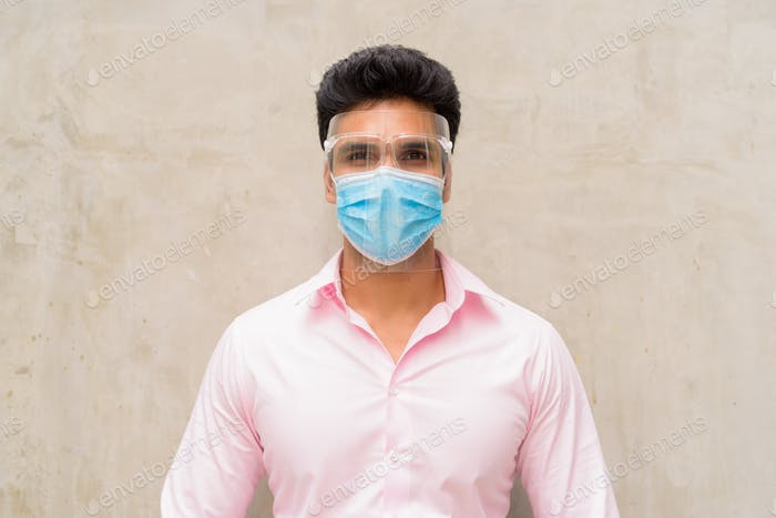 Young Indian businessman wearing mask and face shield for protection from corona virus outbreak