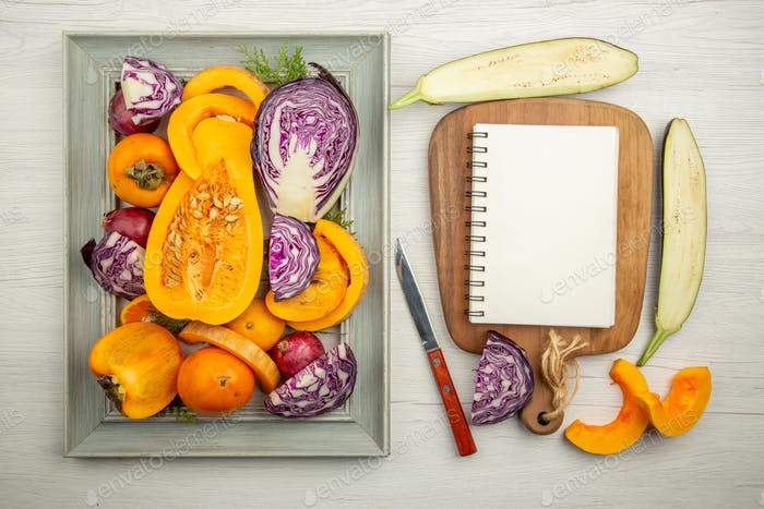 top view chopped red cabbage cut squash persimmon notepad on cutting board knife cut eggplants on