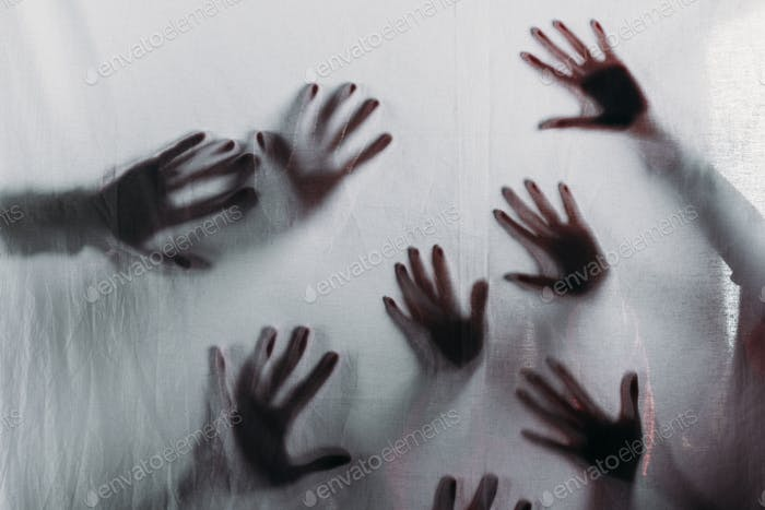 blurry scary silhouettes of human hands touching frosted glass