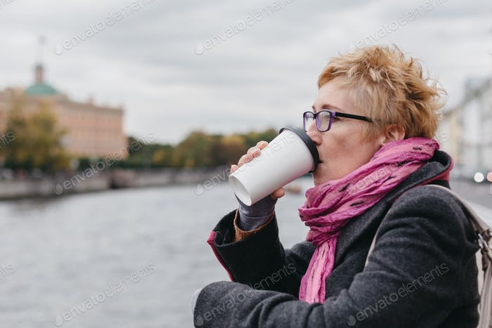 Woman drinking coffee on waterfront