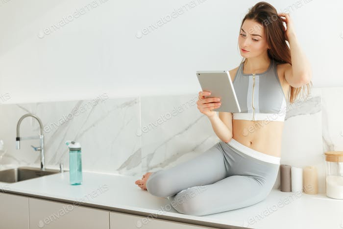Thoughtful lady in sporty top and leggings sitting on kitchen table with tablet in hand