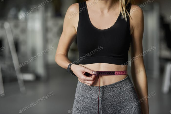 Close up of woman with measuring tape at the gym