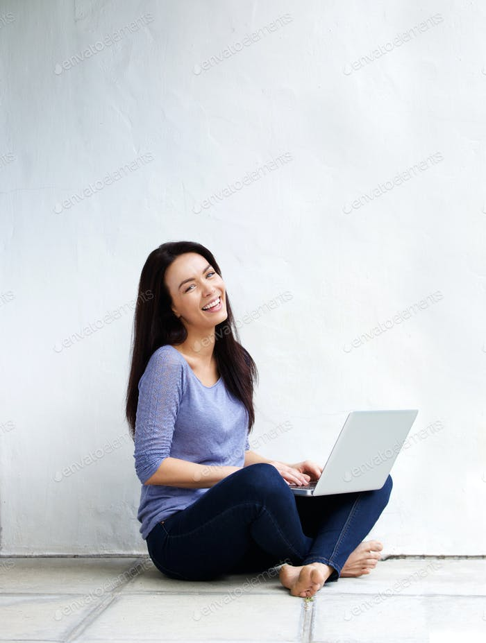 Happy young woman sitting on floor at home with a laptop